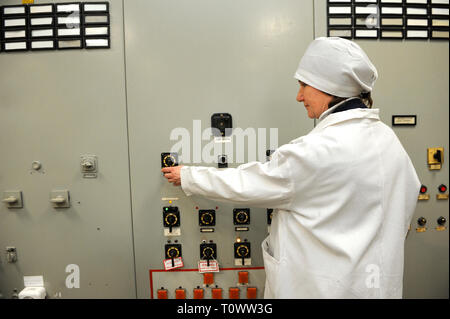 At the control operations room of the Chernobyl Nuclear Power Plant . Operator turning the toggle switch on the main control board. - Stock Photo