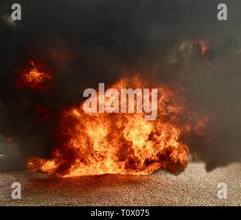 Explosive, dangerous inferno fire with undulating, dancing flames and blackening smoke rising and billowing cloud and plumes of smoke. - Stock Photo