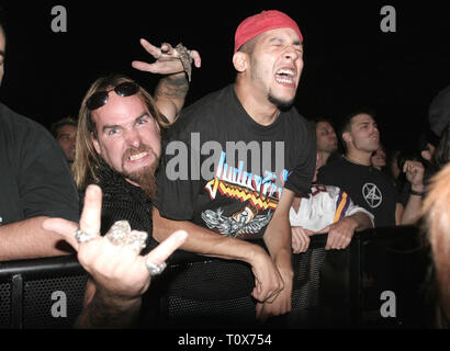Front row fans are shown pumped up during a 'live' concert performance. - Stock Photo