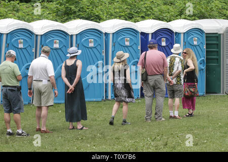 Concert goers are shown waiting their turn in line during an outdoor concert festival. - Stock Photo