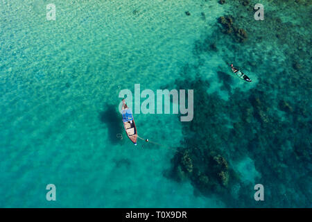 View from above, stunning aerial view of two traditional long-tail boats floating on a turquoise and clear sea. - Stock Photo