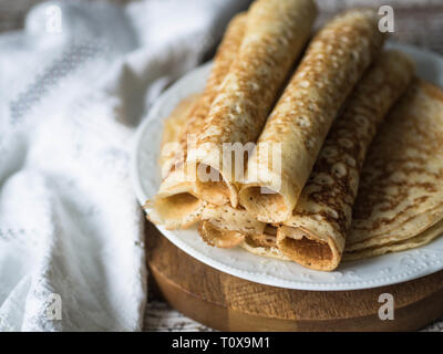 Russian homemade yeast pancakes rolled into a tube on white plate. Traditional wheat pancakes for Shrovetide. - Stock Photo