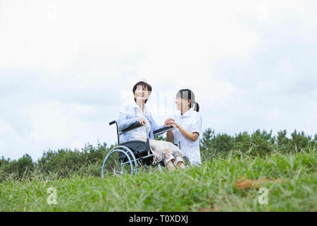 Japanese caretaker helping senior patient - Stock Photo
