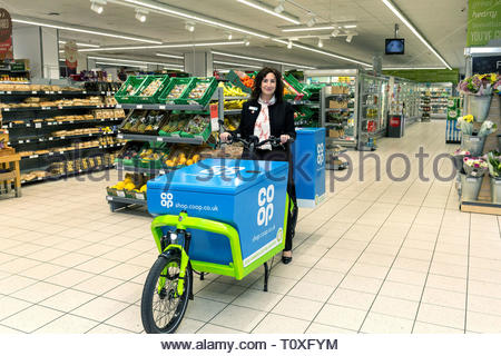 Undated handout photo issued by the Co-op shows Jo Whitfield, CEO Co-op Retail with one of the new home delivery bikes at the Coop Chelsea store, London. - Stock Photo