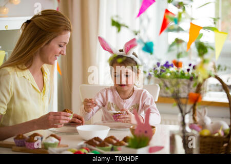 Mother and daughter celebrating Easter, cooking cupcakes, covering with glaze. Happy family holiday. Cute little girl in bunny ears. - Stock Photo
