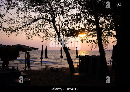 beautiful purple sunset on Pattaya beach with a view of the sun beds and umbrellas in the shade.