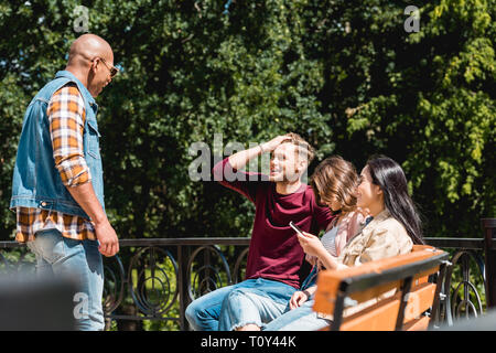 selective focus of cheerful multicultural friends smiling in park - Stock Photo