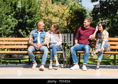 cheerful multicultural friends sitting on benches in park - Stock Photo