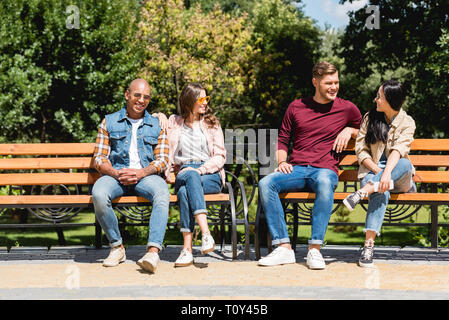 cheerful multicultural friends smiling while sitting on benches in park - Stock Photo