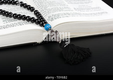 Closeup of opened Holy Bible and rosary beads with cross on black background. Religion concept. Cyrillic text.