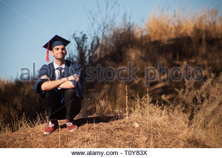 Happy handsome young male in graduation robes and hat with red tassel and shoes. college graduate in cap and gown looking off into the distance. - Stock Photo