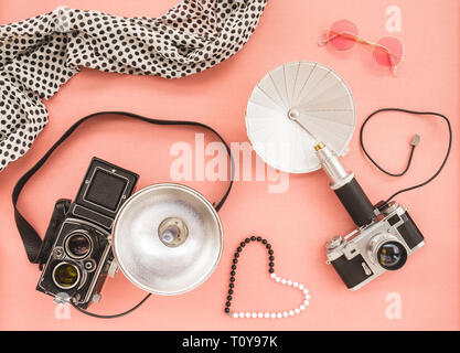 Vintage photo cameras with flashes, on pink canvas background. - Stock Photo