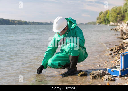 Water quality inspector filling up sample container with river water - Stock Photo
