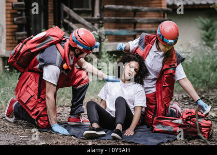 Rescue team helping injured woman. - Stock Photo