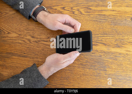 Man holding a smart phone in hands while waiting to be served at restaurant. Phone with empty black curved screen - Stock Photo