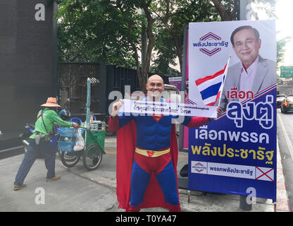 Bangkok, Thailand. 22nd Mar, 2019. The German-Thailander David Pfizenmaier (40) from Waiblingen is on his way as 'Superman' on the streets of Thailand's capital Bangkok to move people to the parliamentary election this Sunday. His banner says, 'If you love Thailand, go vote.' Five years after the recent military coup, more than 51 million people have been called upon to vote. Pfizenmaier stands before an election poster of the incumbent Prime Minister, General Prayut Chan-o-cha. (to dpa: 'Thai Swabian wants to make people vote as 'Superman') Credit: Christoph Sator/dpa/Alamy Live News - Stock Photo