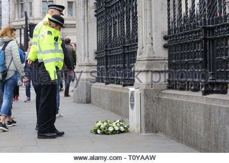 London, UK. 22nd Mar, 2019. Police constables pause at the memorial to PC Keith Palmer in Westminster. Today is the second anniversary of his death which occurred during the attack on London Bridge and fresh flowers have been placed there. Credit: Clearpix/Alamy Live News - Stock Photo