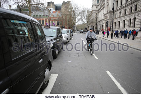 London, UK. 22nd Mar 2019. A cyclist makes progress through the blocked streets around Parliament Square this afternoon. A taxi protest is currrently taking place there and has brought traffic to a standstill in a number of streets. In particular, the drivers are protesting against Sadiq Kahn's plans to ban taxis from certain roads in the capital. Credit: Clearpix/Alamy Live News - Stock Photo