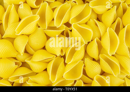 Background of scattered uncooked Italian conchiglie pasta shells - Stock Photo