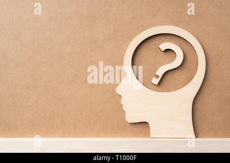 Business and design concept - wooden man head silhouette with question icon on kraft paper - Stock Photo