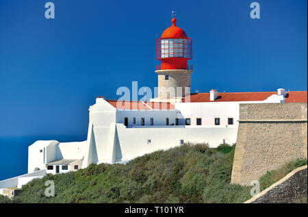 White washed building with red lighthouse contrasting to baby blue sky on a sunny day - Stock Photo