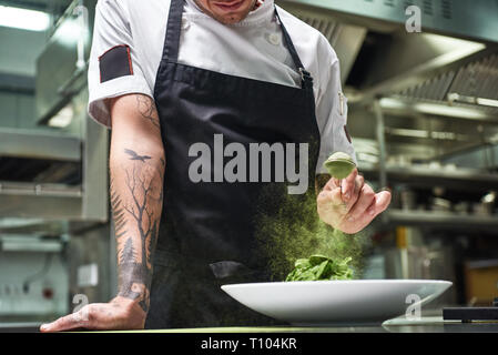 Slow motion. Cropped image of chef's hands with tattoos adding spices in salad while standing in a restaurant kitchen. Food concept. Food conept. - Stock Photo