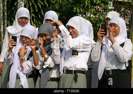 Muslim Girls Taking Photos In Medan, Sumatra - Stock Photo