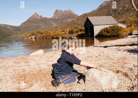 A young 3 year old boy playing in the pebbles by Dove Lake at Cradle Mountain, Tasmania, Australia - Stock Photo