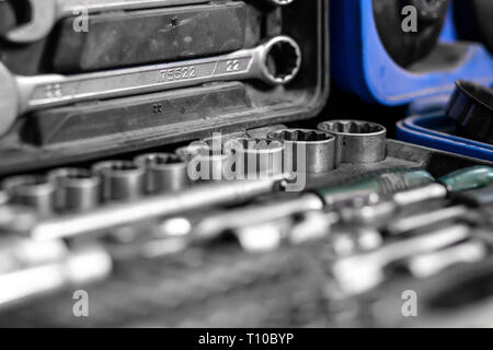 Flat Lay metal tools: wrenches, ratchet, a set of interchangeable heads of different sizes and other tools are in the tool box, a top view. Close-up C - Stock Photo