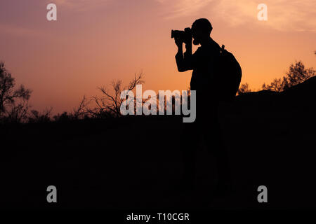 silhouette a beardedphotographer taking photo of sunset light.. A photographer shoots photo late in the evening - Stock Photo