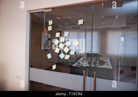Blank colored sticky note or post note stuck on glass wall at office. - Stock Photo