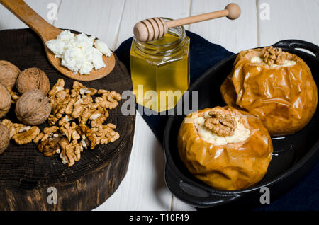 Baked apples with cottage cheese and nuts lie in a black baking dish on a white wooden table next to a jar of honey and a wooden board on which nuts l - Stock Photo