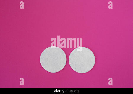 top view on white round cotton disks laid out on a pink background. - Stock Photo