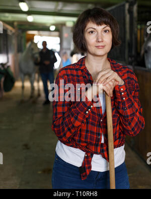 Portrait of young attractive woman who works at horse stable - Stock Photo