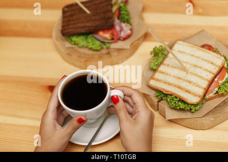 Two sandwiches and cup of hot coffee, on wooden table. Woman hands takes cup. - Stock Photo