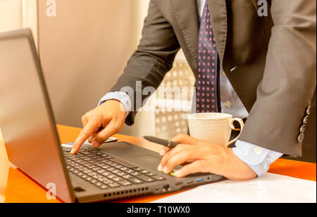Businessman hand press enter laptop keyboard with cup of coffee on the table. - Stock Photo