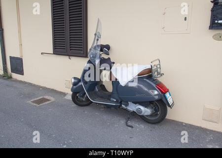 Italy, Montecatini Alto - April 25 2017: the view of Vespa scooter stands parked near the concrete on April 25 2017 in  Tuscany, Italy. - Stock Photo