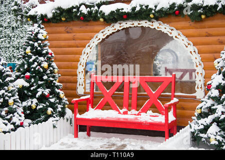 New Year's landscape. Red bench on the background of trees and a wooden hut. Scenery for the new year.Wooden house bench christmas tree - Stock Photo