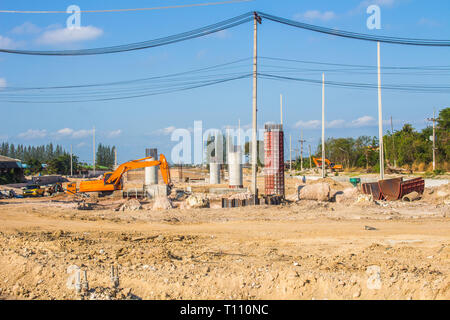 Excavators are digging soil to build bridges across the intersection. Close to the community area - Stock Photo