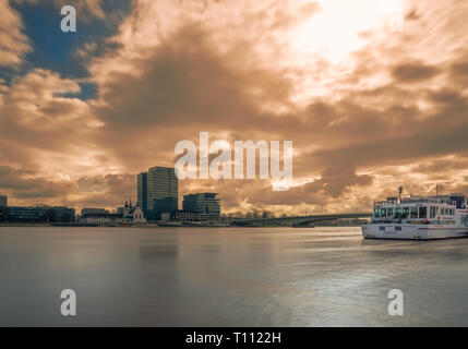 Long Exposure of the River Rhine, a colorful glowing Sky, Ships and a modern Skylines at High Water Level in Cologne Germany in 2019.