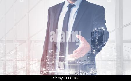 businessman shaking hands, man in suit offering hand for handshake, skyline double exposure - Stock Photo