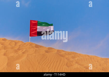 UAE Flag blowing in the wind on the top of an orange sand dune in the blue sky in Ras al Khaimah, United Arab Emirates. - Stock Photo