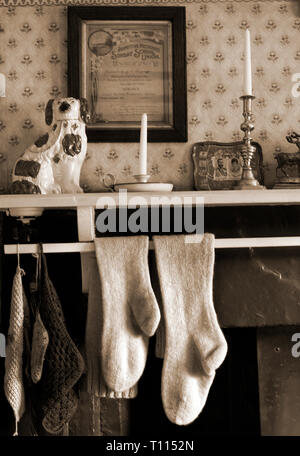 hand knitted socks hanging on vintage mantlepiece to dry - Stock Photo
