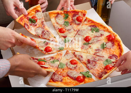 Friends taking slices of pizza from cardboard box - Stock Photo