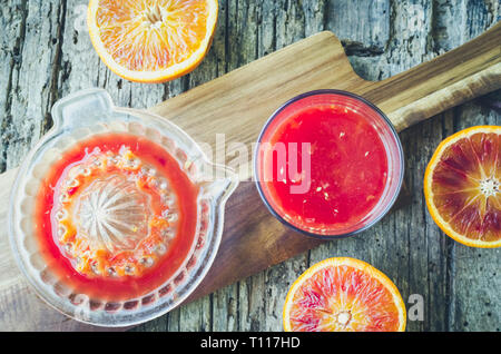 Preparation of Sicilian blood oranges juice on old wooden textured background. Freshly squeezed juice in a glass. Top view. - Stock Photo