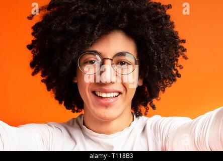 Cheerful millennial african-american guy making selfie on orange - Stock Photo