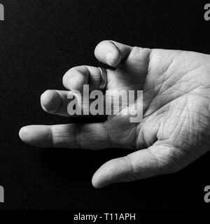 Black & white image of man`s hand, open palm up and pointing, isolated against a black background with dramatic sidelight. - Stock Photo