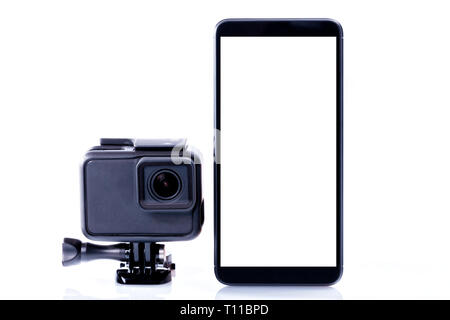 A modern video sports camera next to a black smartphone with screen in blank isolated on white. - Stock Photo