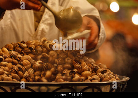 Vendor dishes up bowl of snails for dinner in Marrakesh market - Stock Photo