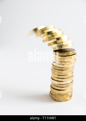 A pile of new one pound sterling coins with the top few toppling over denoting a collapse of the currency - Stock Photo